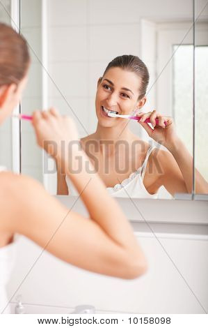 Young woman brushing teeth in front of mirror