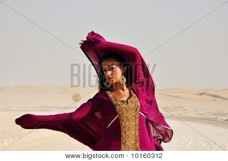 Lovely Young Woman Wearing Purple Eastern Dress In Arabic Desert