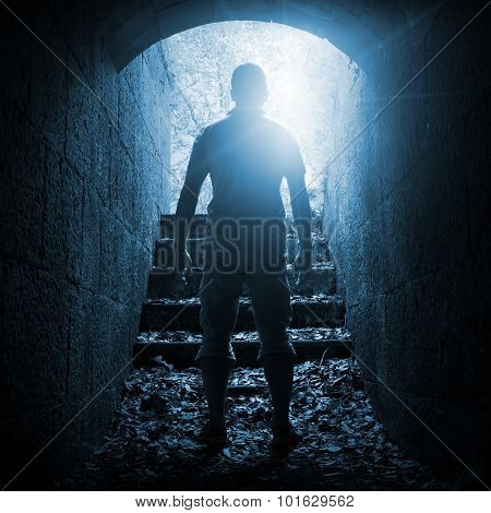 Young Man Stands In Dark Stone Tunnel, Blue Toned