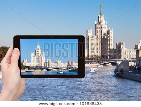 travel concept - tourist photographs picture high-rise apartment building on Kotelnicheskaya Embankment in Moscow on tablet pc poster