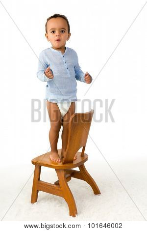 Cheerful little 18 month old toddler boy standing on a small wooden chair