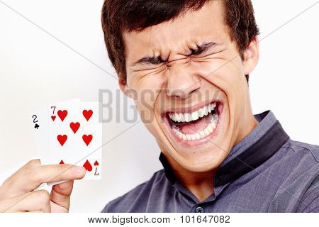 Close up portrait of young hispanic man wearing grey shirt holding 2-7 (worst standard poker starting hand) in his hand and loudly screaming against white wall - gambling failing concept