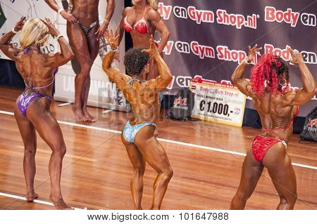 Three Female Bodybuilders In Back Double Biceps Pose On Stage