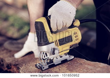 Carpenter is cutting wood with fret saw, toned
