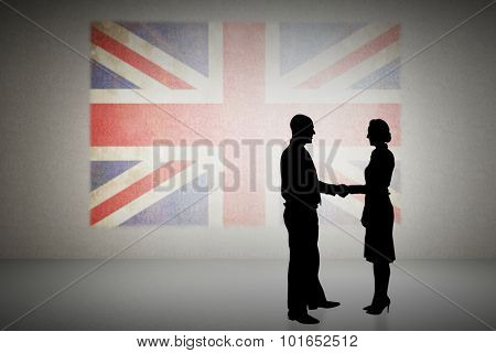 Silhouettes shaking hands against union jack flag in grunge effect