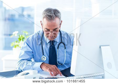 Male doctor reviewing document at desk in hospital