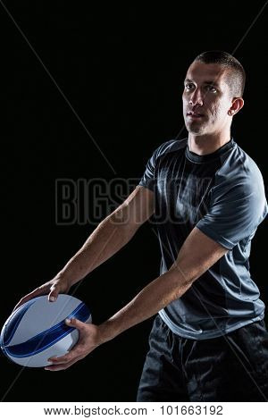 Focused rugby player looking away while holding ball against white backgound