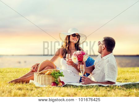 love, dating, people and holidays concept - smiling couple drinking champagne on picnic over evening seaside background poster