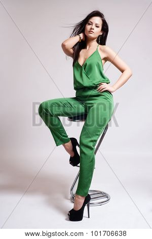 Fashion Dressed Sexy Girl Sitting on Chair. Full length Portrait. Beauty Woman isolated on White. Wo