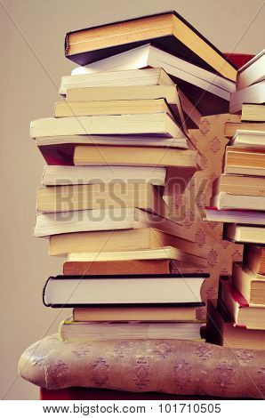 closeup of some piles of books on an old chair, with a retro effect
