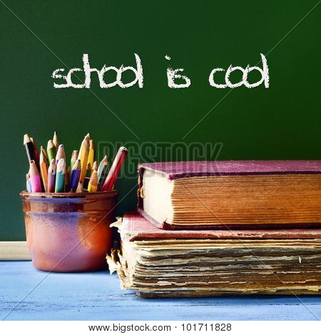 some pencils in a pot, some books on a blue school desk, and the text school is cool written with chalk in a chalkboard
