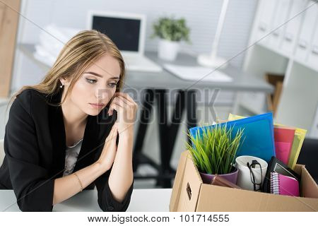 Young Dismissed Female Worker In Office Sitting Near Carton Box With Her Belongings
