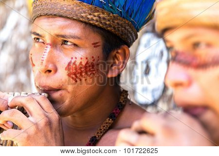Native Brazilian guys playing wooden flute at an indigenous tribe in the Amazon