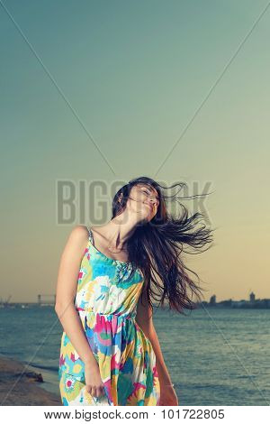 Waist Up Shot of Young Women on Seaside with wind fluttering her hair