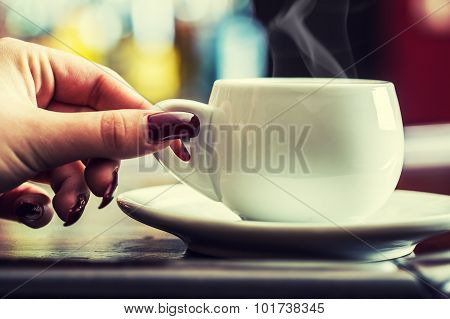 Woman's hand with red manicured nails holding a cup of coffee.