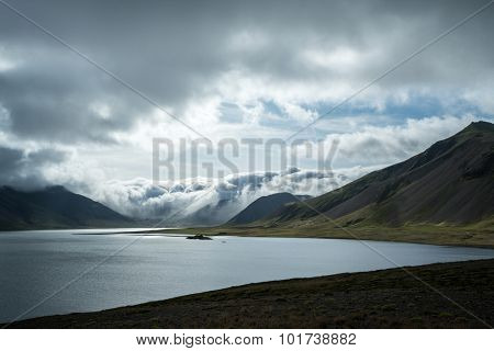 storm clouds, mountains, valleys and lake on a summer afternoon in Iceland