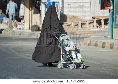 Arabic woman in hijab conducts carriage with child