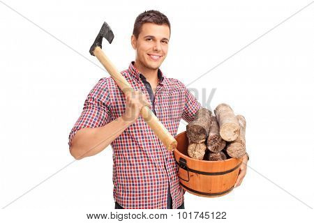 Young man carrying an axe over his shoulder and holding a bucket full of logs isolated on white background