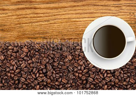 Close-up Of Roasted Coffee Beans And Coffee Cup Over Wooden Background