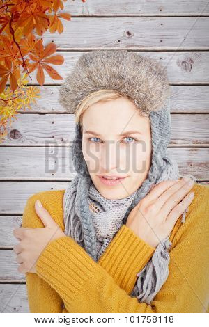 Woman in winter clothes shivering over white background against autumn leaves pattern