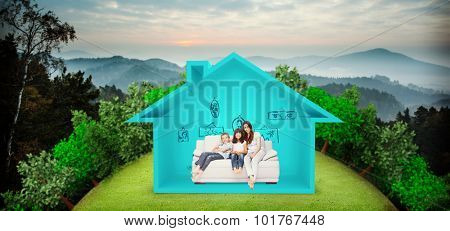 Mother with their children sitting on sofa against trees and mountain range against cloudy sky