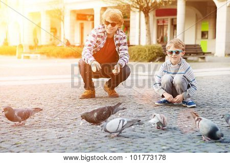 Two Boys Feeding Doves On City Square