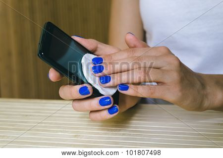 Female hands with blue manicure wipe dust touch screen mobile phone poster