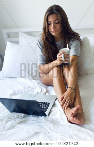 Beautiful Young Woman Using Her Laptop Amb Drinking Coffee At Home.