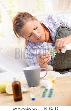 Woman Having Flu Taking Medicines In Bed