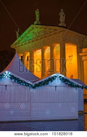 Illuminated Vilnius Cathedral And Christmas Market Kiosk In Holiday Decoration