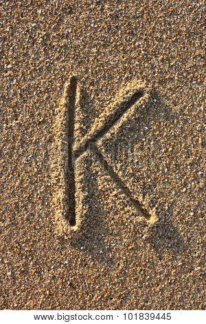Alphabet's letter K handwritten in sand on the beach, at sunrise.