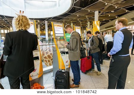 DUSSELDORF, GERMANY - SEPTEMBER 16, 2014: passengers use self check-in kiosks in airport. Dusseldorf Airport is the international airport of Dusseldorf