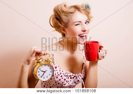 Smiling housewife with alarm-clock and cup