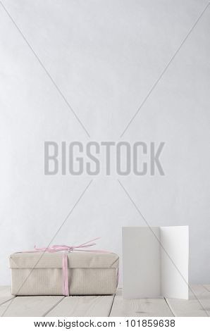 Wrapped Gift Box On Table With Icy Pink Raffia And Greeting Card