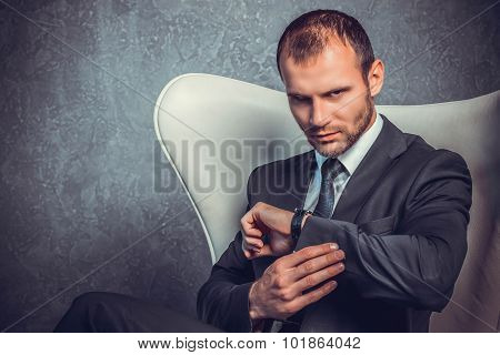 Brutal sexy businessmen in suit with tie sitting on the chair. Boss concept.