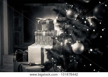 Monochrome Photo Of Christmas Gifts On Floor Next To Decorated Fir Tree