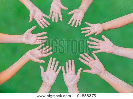 Arms Of Children Together In Circle On Green Background