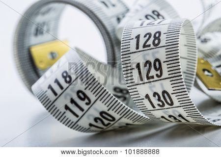 Curved measuring tape. Measuring tape of the tailor. Closeup view of white measuring tape poster