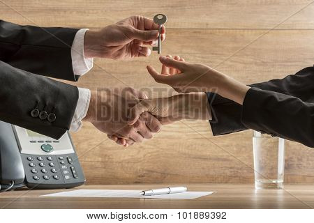 Successful business deal - real estate agent and new female homeowner exchanging house key while shaking hands over a contract of house sale. poster