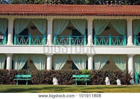 Facade Of Summer Resort Villa With Balconies In Scenary Garden