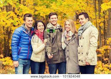 season, people, technology and friendship concept - group of smiling friends with smartphone and selfie stick taking picture in autumn park
