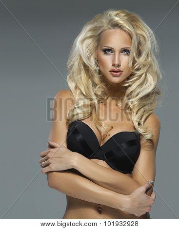 Beautiful blonde woman posing in sensual underwear looking at camera. Perfect fitness body.
