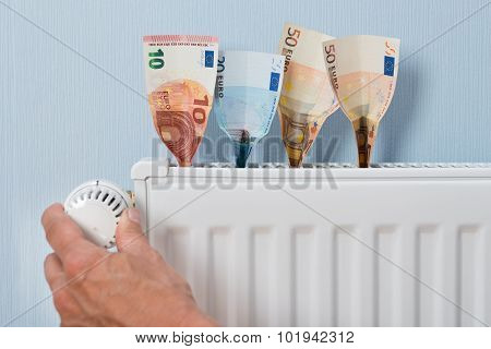 Man Holding Thermostat With Banknotes