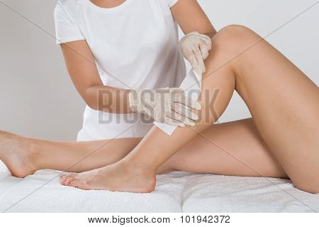 Beautician Waxing Leg Of Woman With Wax Strip At Beauty Clinic poster