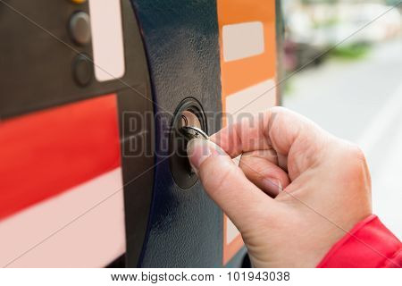 Person Hands Inserting Coin Into Parking Meter