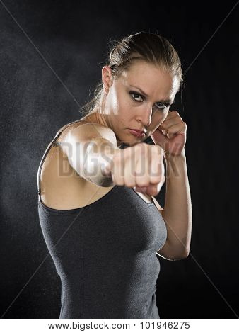 Female Fighter in Combat Pose Against Black