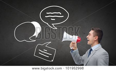 business, people, information and communication concept - happy businessman in suit speaking to megaphone and text bubbles over dark gray concrete wall background