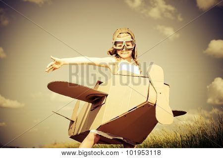 Little dreamer girl playing with a cardboard airplane in the field over sky and white clouds. Childhood. Fantasy, imagination. Retro style, sepia.