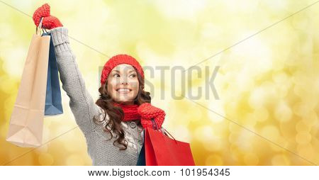 holidays, christmas, x-mas, sale and people concept - happy young asian woman in winter clothes with shopping bags over yellow lights background