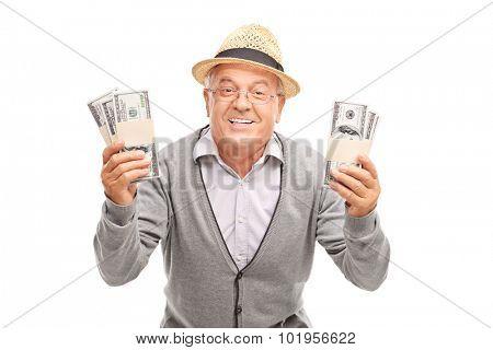 Overjoyed senior gentleman holding two stacks of money and smiling isolated on white background